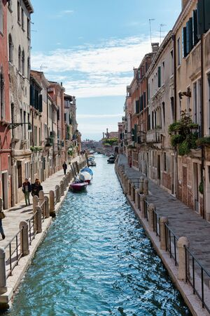 residential building: View of Canal and Pedestrians on Waterfront Promenades Through Residential Building Lined Street Scene in Venice, Italy on Sunny Day with Blue Sky