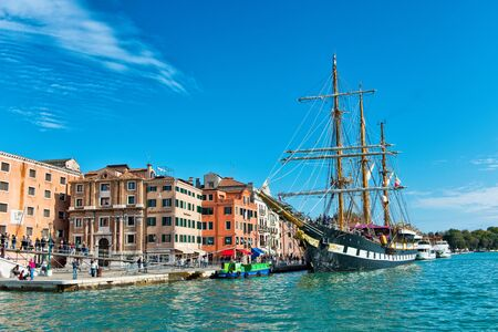 palinuro: Italian Navy historic training barquentine, the Palinuro, moored on the riva in Venice, Italy in the Giudecca Canal in front of a colorful old palazzo Editorial