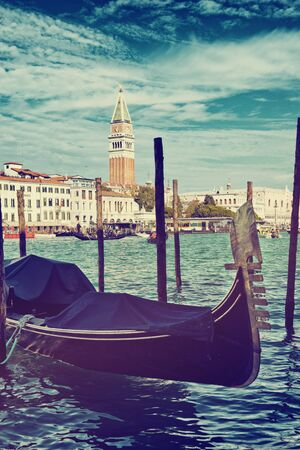 washed out: Toned moody image of gondolas moored in the Grand Canal in Venice, Italy with a view across the water to the Campanile