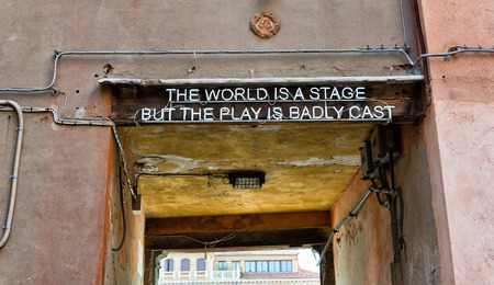 badly: Quotation over a doorway entrance to a thoroughfare in Venice, Italy saying - The world is a stage but the play is badly cast