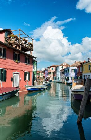italy street: Typical street scene in Burano, near Venice, Italy with vivid its colorful brightly painted houses and a canal with a fishing boat