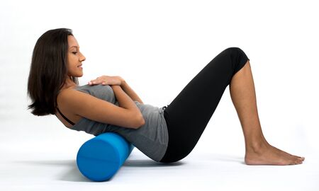 woman profile: Side Profile View of Young Brunette Woman Doing Sit Up Crunches with Exercise Roll Aid in White Studio - Cut Out of Woman Exercising on Floor