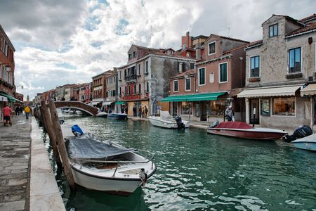 canal street: Street scene with a canal and moored boats in Murano, Italy Editorial