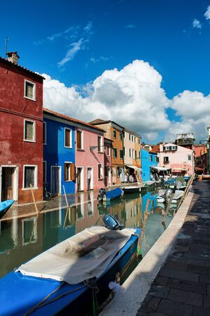 city park boat house: Typical street scene in Burano, near Venice, Italy with vivid its colorful brightly painted houses and a canal with a fishing boat