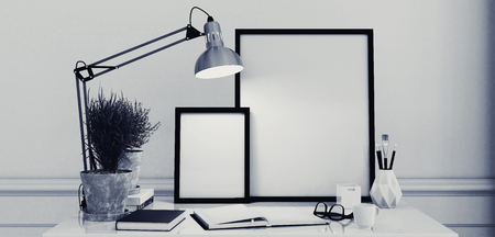 Blank picture frames on a simple modern desk or writing table with an open journal and anglepoise lamp in monochromatic black and white decor, 3d rendering
