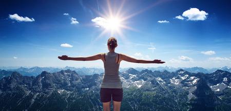 Jonge vrouw vieren natuur stond met open armen met uitzicht op een panoramische scène van alpine bergtoppen met een strak effect en zonnestraal Stockfoto