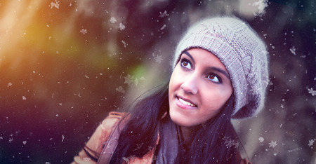 wonderment: Attractive young Indian woman in a knitted winter hat watching the snow falling with a smile of pleasure and wonderment over a blurred outdoor background with copy space Stock Photo