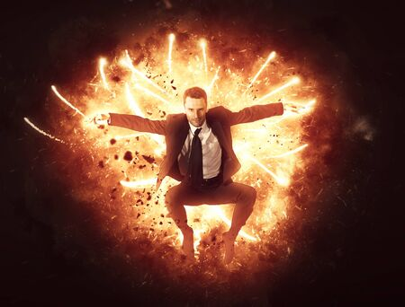 Businessman bursting through a wall of fire with flying explosive sparks in a conceptual image of power, energy, ambition, motivation and success
