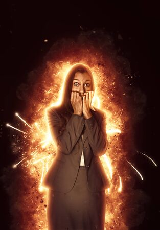 engulfed: Panic stricken young Indian businesswoman surrounded by burning flames staring wide-eyed at the camera and biting her nails in a conceptual image over a dark shadowy background