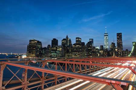 streaking: View of Manhattan Skyline Illuminated with Lights at Night from Brooklyn Bridge, Streaking Vehicle Head Lights Crossing Bridge Over East River, New York City, New York, USA Stock Photo