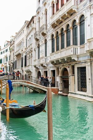 fare: View of the end of a gondola waiting for a fare in front of a bridge over a canal lined with historic buildings with tourists crossing over sightseeing in Venice, Italy Stock Photo