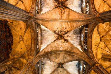roman pillar: Low Angle Architectural View of Interior of Historic Barcelona Cathedral, Looking Up at Vaulted Nave Ceiling Illuminated in Warm Light Editorial