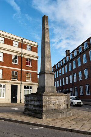hants: Old monument obelisk in center of converging roads among brick buildings in the United Kingdom Editorial