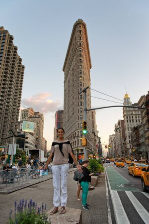 flatiron: Full Length of Happy Smiling Female Tourist Standing on Median at Busy Fifth Avenue Intersection in front of Historic Flatiron Building at Dusk, Manhattan, New York City, New York, USA