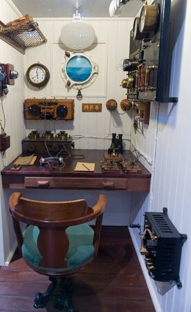 titanic: Museum exhibit display of communications room with tiny porthole, chair and various radios in old ship