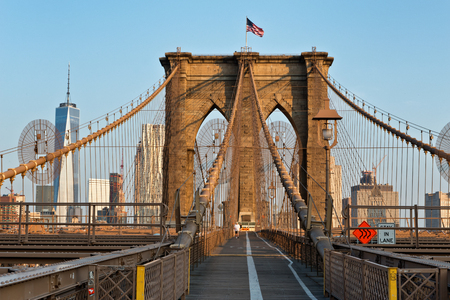 bridges: The New York City Brooklyn Bridge Wooden pedestrian walkway with flag up top and city skyline behind it Stock Photo