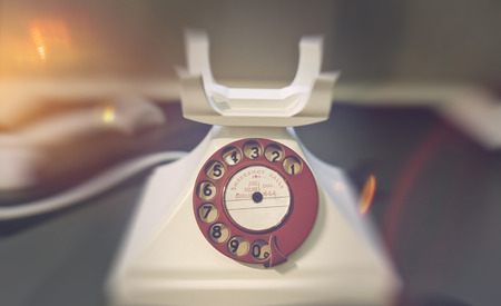 telephonic: Blurry edges around close up of old telephone with rotary dialer and receiver off the hook