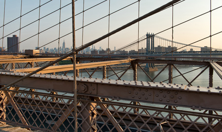 girders: View of Empire State Building, Manhattan Bridge and Hazy City Skyline Through Support Cables and Past Girders of Historic Brooklyn Bridge at Warm Sunset, New York City, New York, USA
