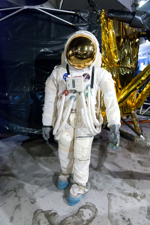 Front view of exhibit of full size astronaut walking on the moon in front of large reproduction of the lunar lander