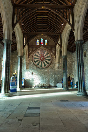 great hall: View inside empty old English building with shield of the knights of the round table on stone wall