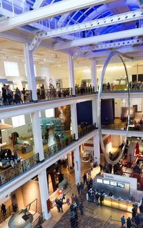 displays: Crowds of people looking at exhibits and displays over the three floors of the Science Museum in London, UK viewed across the entrance hall or atrium