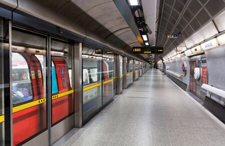 hants: View from platform of red high speed subway train station behind closed doors Editorial