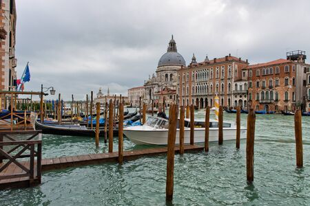 moorings: Motorboat moored in the Grand Canal, Venice alongside a jetty with the Basilica Santa Maria della Salute in the background Editorial