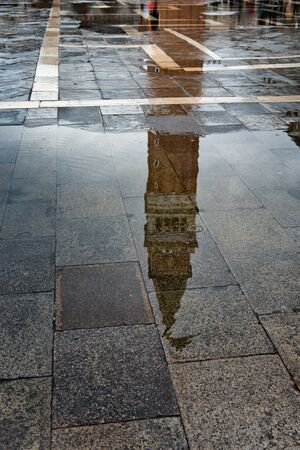 the campanile: Saint Mark campanile or bell tower reflected on the wet stone pavement of the famous square in Venice, Italy