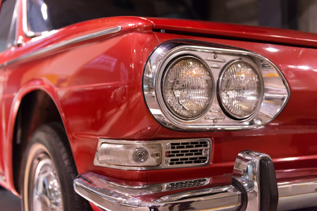 dual: Close up of vintage red automobile front with dual headlights, bumpers and highly polished shiny chrome finish Stock Photo