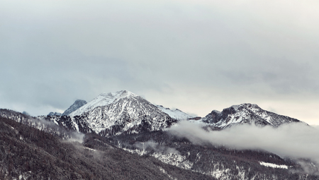 dreary: Tranquil scene of the Alps and slow thick clouds surrounding them with foothills in foreground during winter season
