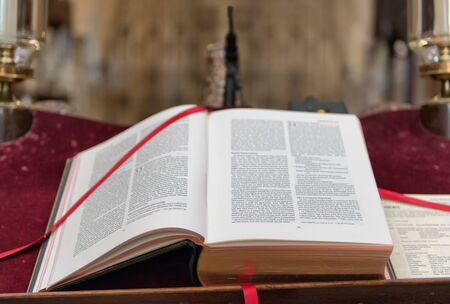preaching: Close up of Christian Holy Bible Old Testament with red book marker on table laced around the top