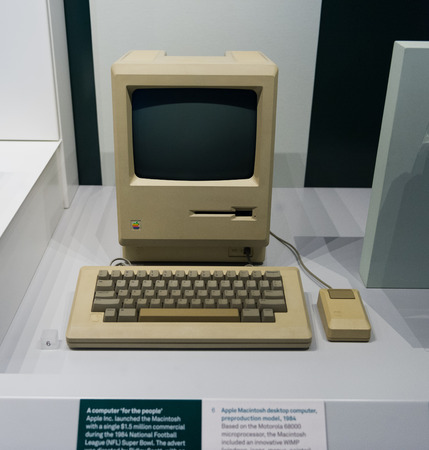 Old original Apple Mac computer with keyboard on display in a glass case in a museum, in London, UK, detailing the advancement of technology