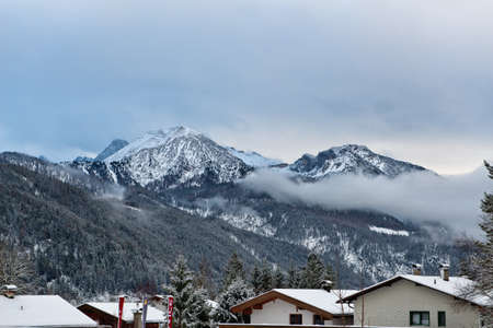 dreary: View of Alps mountain peaks and slow moving clouds around them with resort in foreground during winter season