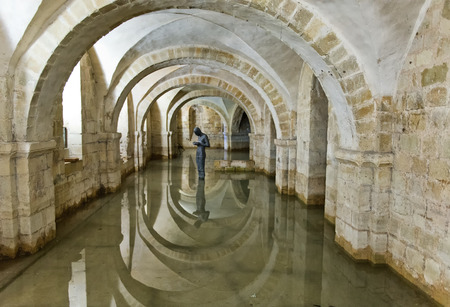 crypt: Winchester, Hampshire, UK - February 07, 2016: The flooded Crypt of Winchester Cathedral containing the sculpture Sound II by british artist Antony Gormley. Winchester, UK on February 07, 2015. Editorial