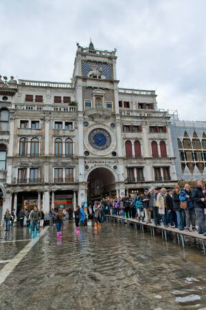 clocktower: VENICE, ITALY - 17 OCTOBER 2015: St. Marks Square (Piazza San Marco) during high tide (acqua alta) in Venice, Italy. Acqua alta is an unusual high tide, which floods parts of Venice. October 17 2015. Editorial