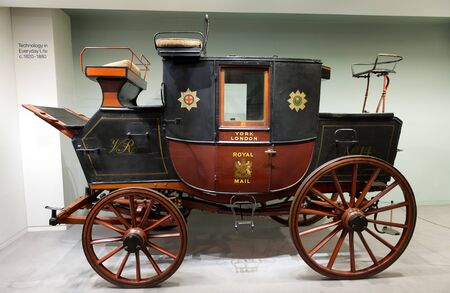 horse drawn: Single restored horse carriage with multiple seats and doors on display in museum gallery Editorial