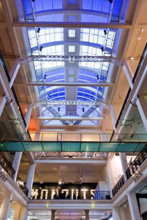 view of an atrium in a building: Entrance hall of the Science Museum, London, UK looking up from below at the domed blue roof with people visible as silhouettes on the floors above