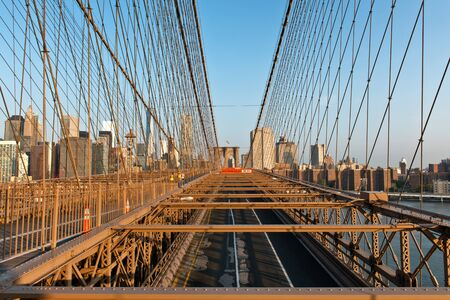 girders: No Traffic on Brooklyn Bridge with Detail of Girders and Support Cables Looking Toward Manhattan City Skyline at Sunset, New York City, New York, USA Stock Photo