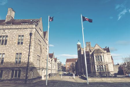 flagpoles: Fluttering flags on flagpoles high up waving in air at front of British historical landmarks from medieval era Stock Photo