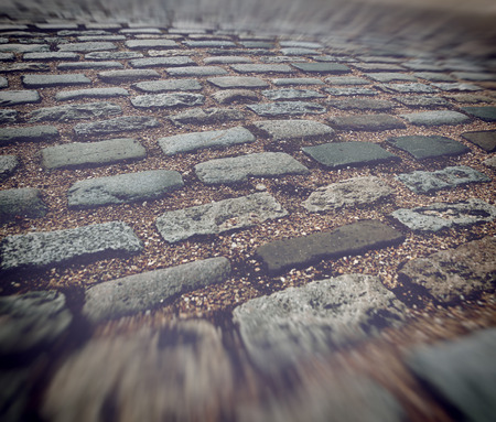 simulating: Close up of old worn out brick paving blocks separated by stones in road with blurry edges simulating motion