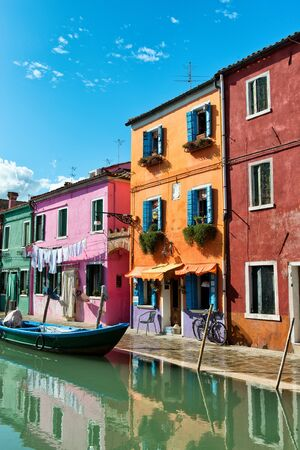 vividly: Colorful vividly painted houses, Burano, Venice, Italy alongside a canal and moored boats traditionally painted in these colors so the fishermen could find their way home in mist