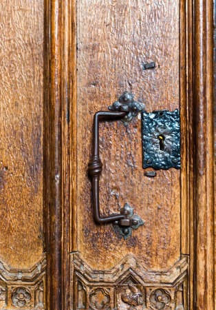 escutcheon: Old iron door handle and escutcheon on a weathered ornately carved ancient gothic wooden interior door in Winchester Cathedral