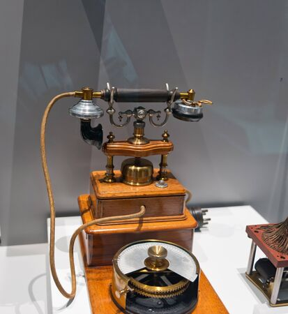 display case: Fancy old wooden telephone in display case for telecommunications exhibit in museum