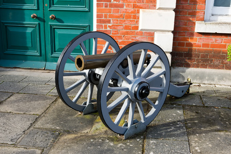 gunnery: Historic antique cannon on wooden wheels locked to the ground outdoors as a display of warfare Stock Photo