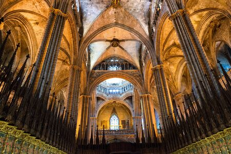 barcelona cathedral: Low Angle Interior View of Historic Barcelona Cathedral with Vaulted Ceiling and Spires Illuminated in Warm Lighting, Barcelona, Spain