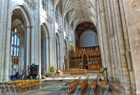 nave: Interior view of the nave of Winchester Cathedral, Winchester, UK showing the high vaulted ceiling and wooden pews