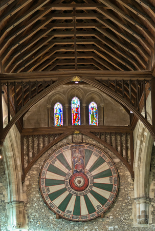 rafters: Low angle view of the Knights of the Round Table Shield on stone wall under wooden rafters at the Winchester Castle in the United Kingdom