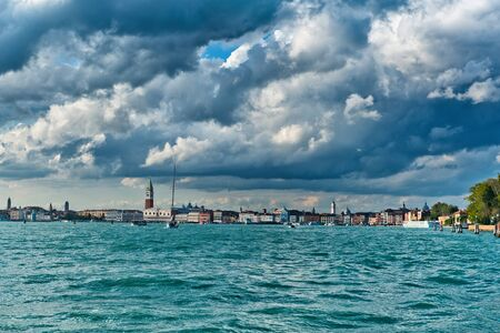cloud formations: Venice skyline viewed from the water across San Marco Basin under dramatic cloud formations looking towards the Campanile and Doges palace in the distance, Italy