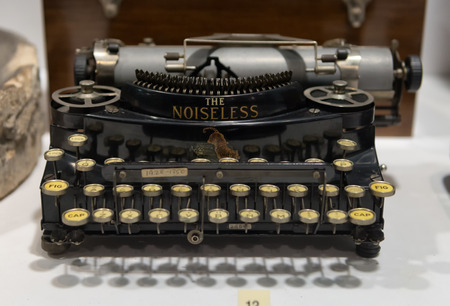 noiseless: Single compact vintage typewriter with exposed ribbon and roller on display inside case at museum