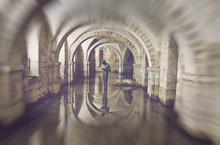 11th century: Winchester, Hampshire, UK - February 07, 2016: The flooded Crypt of Winchester Cathedral containing the sculpture Sound II by british artist Antony Gormley. Winchester, UK on February 07, 2015. Editorial